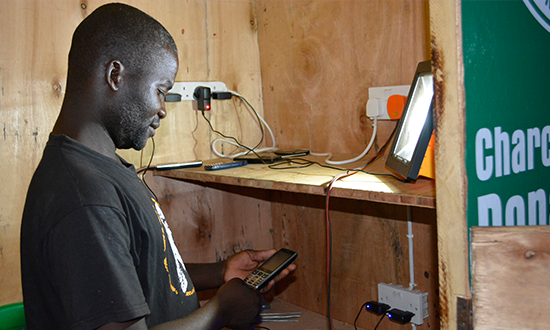 Biston operating the kiosk for charging phones donated by ESCOM at Chikuse camp in Nchalo.